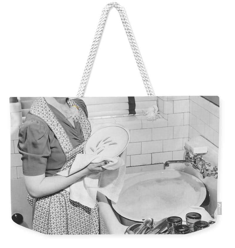 Three Quarter Length Weekender Tote Bag featuring the photograph Woman Drying Dishes At Kitchen Sink by George Marks