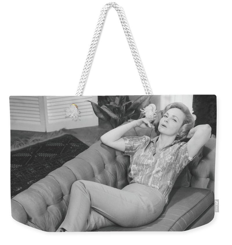 Smoking Weekender Tote Bag featuring the photograph Woman Relaxing On Sofa, B&w, Elevated by George Marks