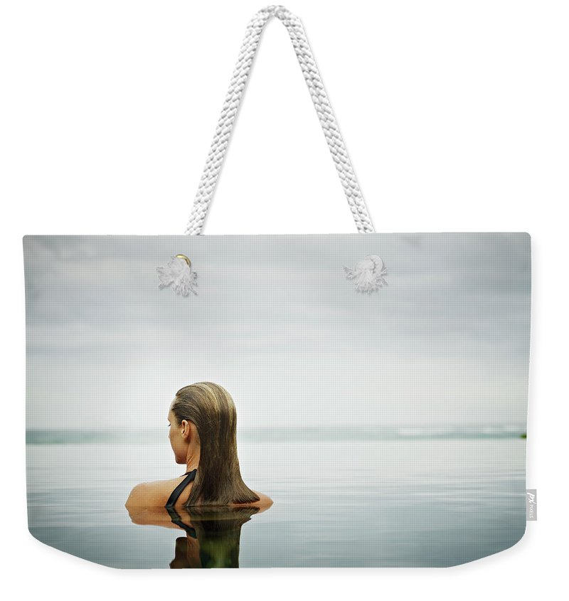 People Weekender Tote Bag featuring the photograph Woman Standing In Infinity Pool by Thomas Barwick