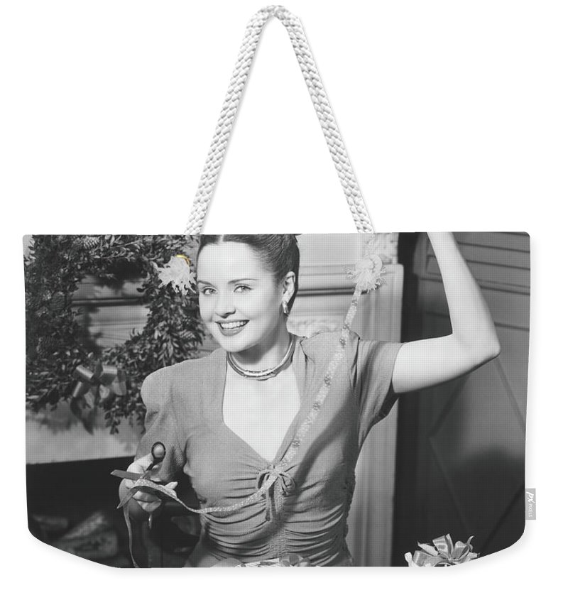 Human Arm Weekender Tote Bag featuring the photograph Woman Wrapping Christmas Presents In by George Marks