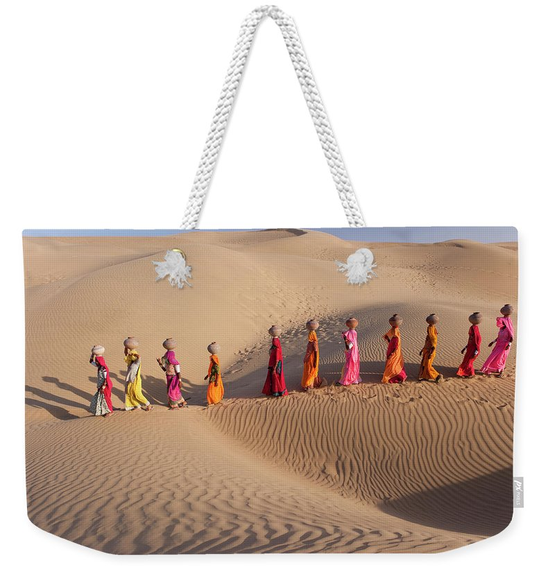 People Weekender Tote Bag featuring the photograph Women Fetching Water From The Sparse by Mint Images - Art Wolfe