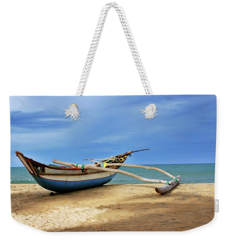 Tranquility Weekender Tote Bag featuring the photograph Wooden Catamaran By The Sea Shore by Juavenita Alphonsus