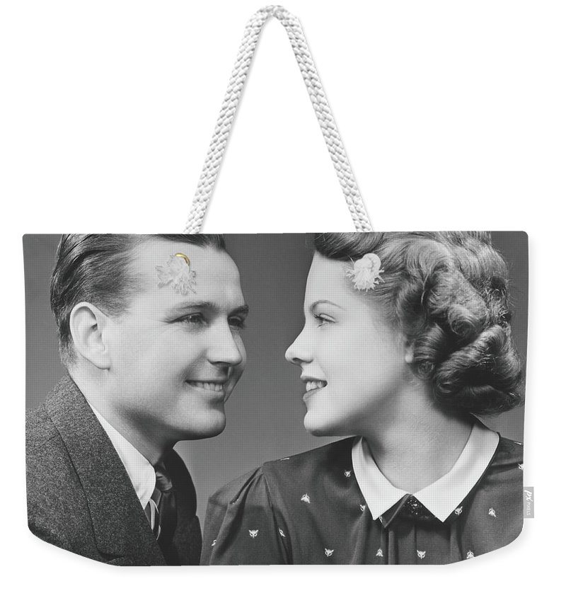 Young Men Weekender Tote Bag featuring the photograph Young Couple Looking In Eyes In Studio by George Marks