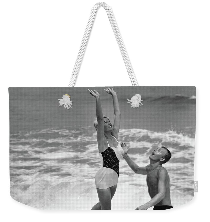 Young Men Weekender Tote Bag featuring the photograph Young Couple Playing With Beach Ball At by Stockbyte