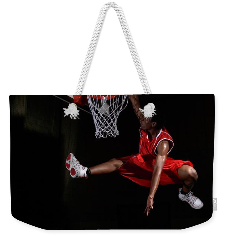 Human Arm Weekender Tote Bag featuring the photograph Young Man Making A Fancy Dunk by Compassionate Eye Foundation/steve Coleman/ojo Images Ltd
