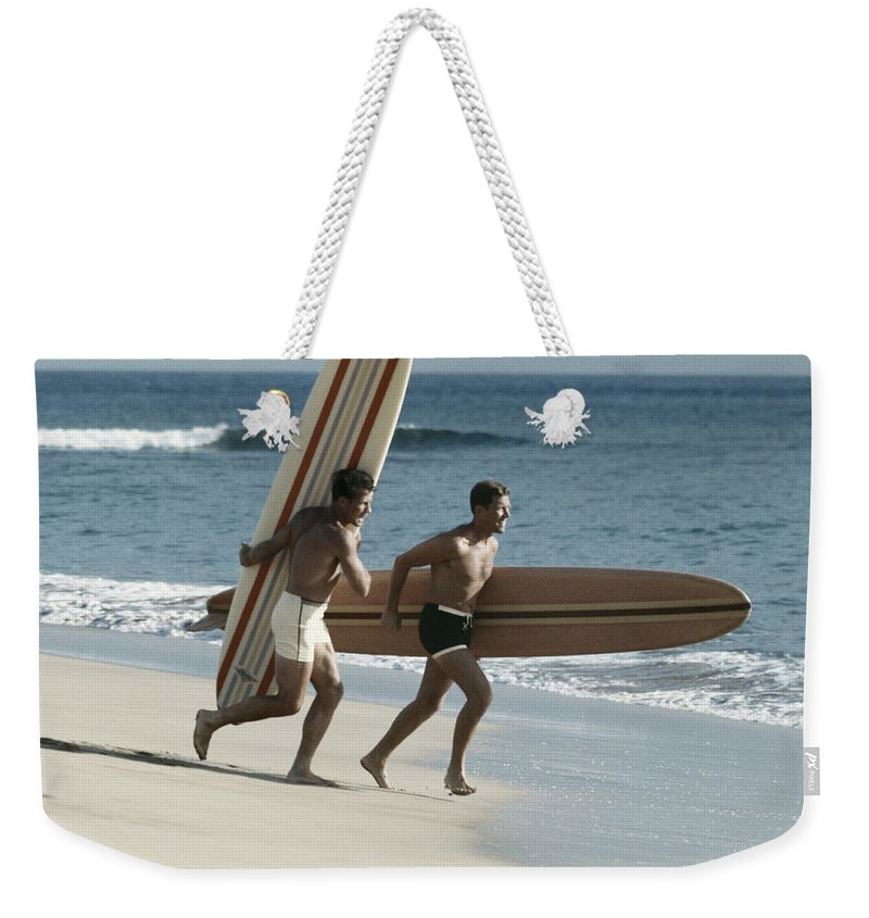 People Weekender Tote Bag featuring the photograph Young Men Running On Beach With by Tom Kelley Archive