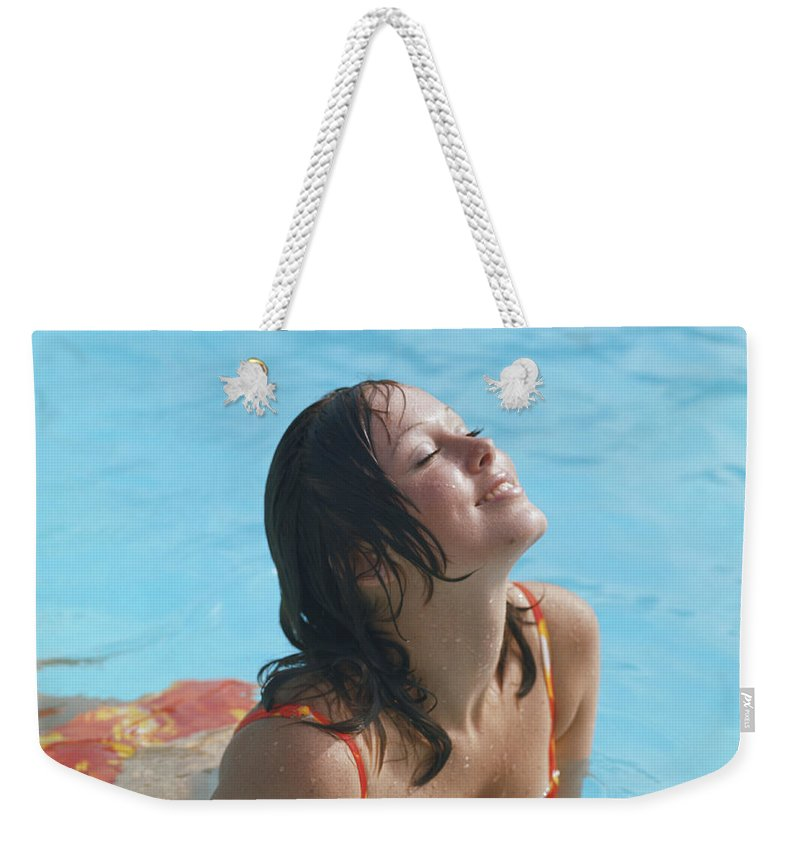 1973 Weekender Tote Bag featuring the photograph Young Woman In Bikini At Swimming Pool by Tom Kelley Archive