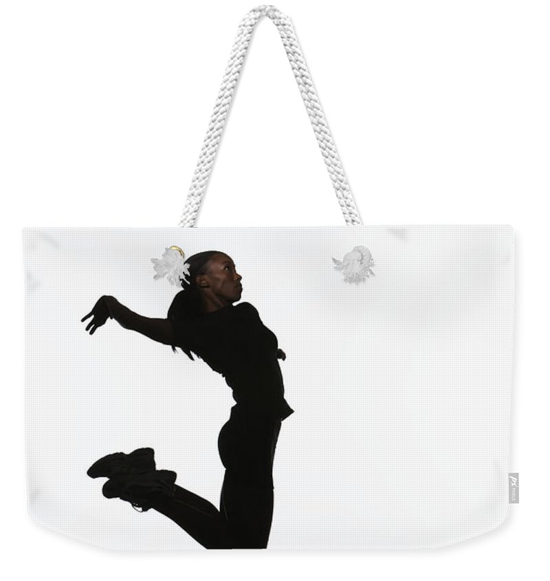 Human Arm Weekender Tote Bag featuring the photograph Young Woman Jumping In Air, Reaching To by Paul Taylor