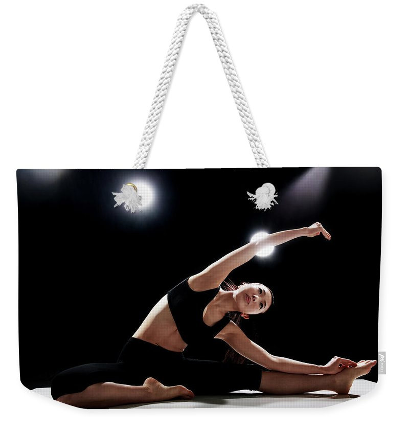 People Weekender Tote Bag featuring the photograph Young Woman Stretching by Runphoto
