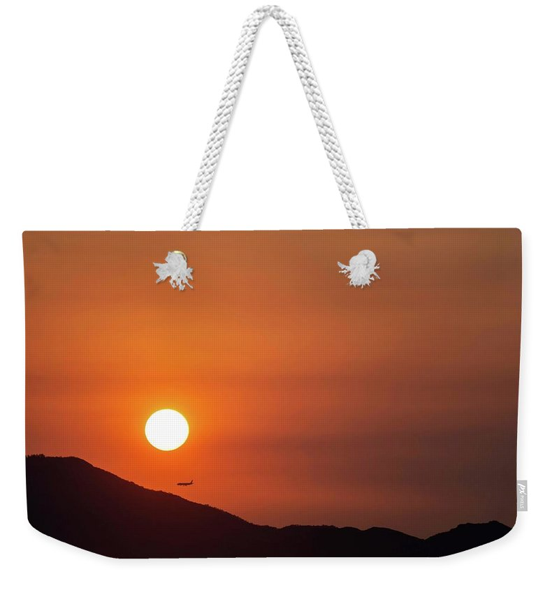 Sunset Weekender Tote Bag featuring the photograph Red sunset and plane in flight by Hannes Roeckel