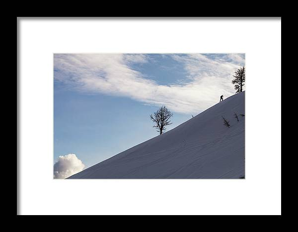 Adventure Framed Print featuring the photograph A Backcountry Skier Skins Up A Ridge by Robin Carleton