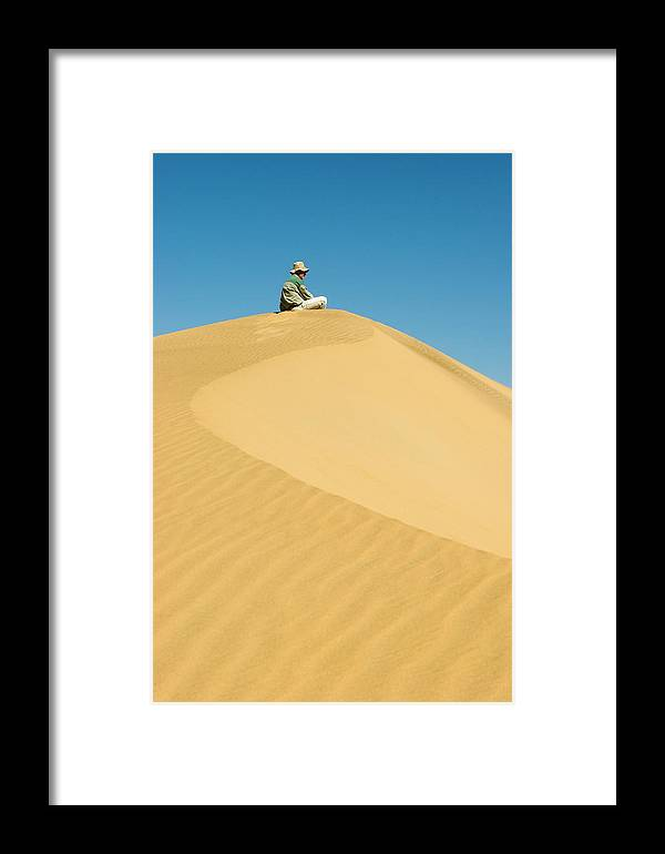 Absense Framed Print featuring the photograph A Man Sits Atop A Dun In The Namib by Jen Judge
