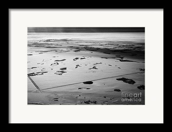 Aerial Framed Print featuring the photograph aerial view of snow covered prairies and remote isolated farmland in Saskatchewan Canada by Joe Fox