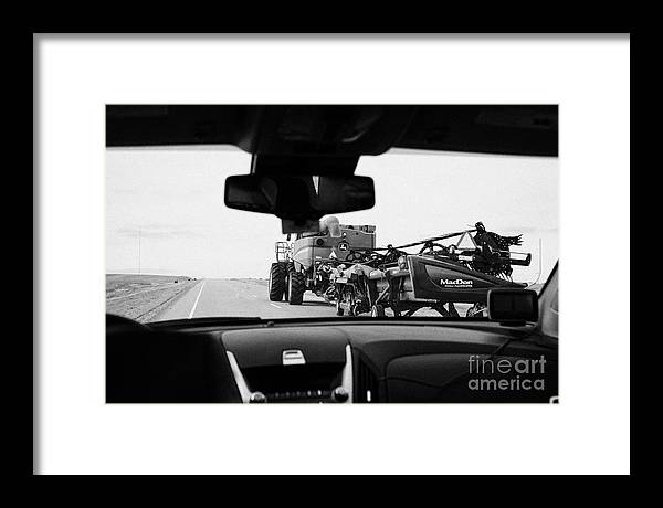 Driving Framed Print featuring the photograph driving behind combine harvester on road in Saskatchewan Canada by Joe Fox
