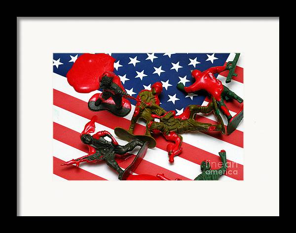 Against The War Framed Print featuring the photograph Fallen Toy Soliders On American Flag by Amy Cicconi