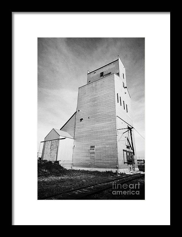 Grain Framed Print featuring the photograph grain elevator and old train track landmark leader Saskatchewan Canada by Joe Fox