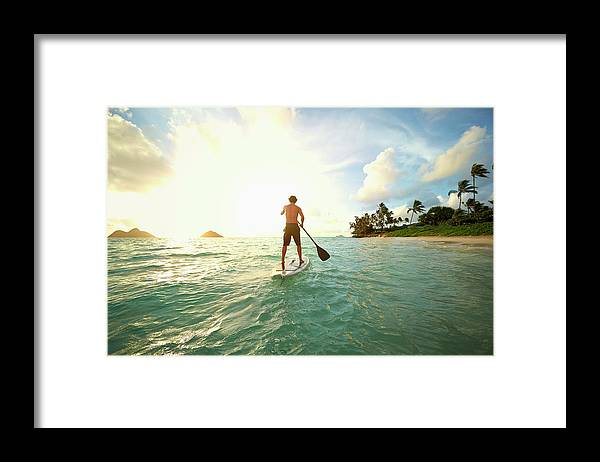 Tranquility Framed Print featuring the photograph Caucasian Man On Paddle Board In Ocean by Colin Anderson Productions Pty Ltd