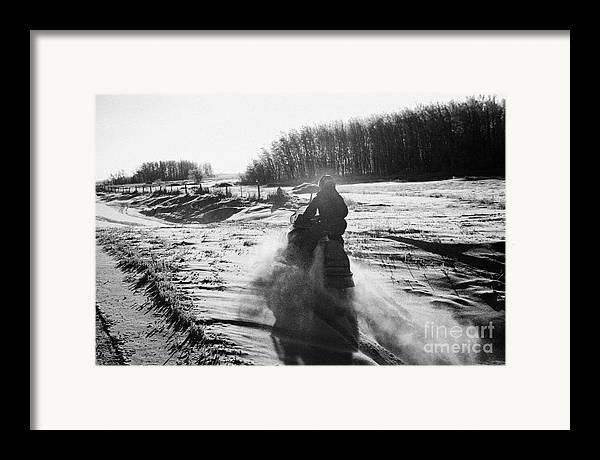 Man Framed Print featuring the photograph man on snowmobile crossing frozen fields in rural Forget Saskatchewan Canada by Joe Fox