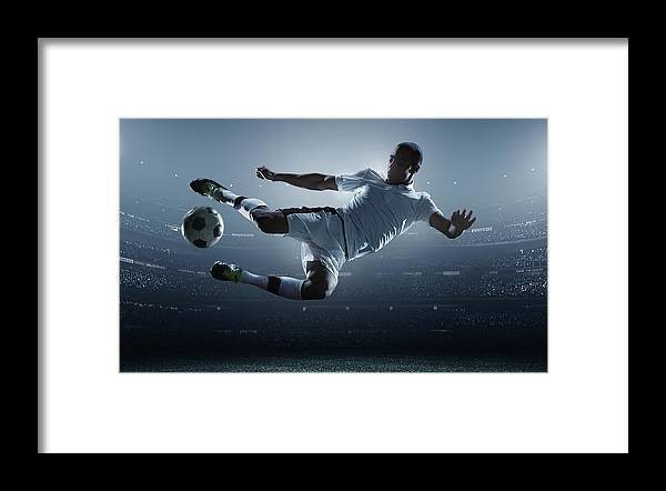 Goal Framed Print featuring the photograph Soccer Player Kicking Ball In Stadium by Dmytro Aksonov