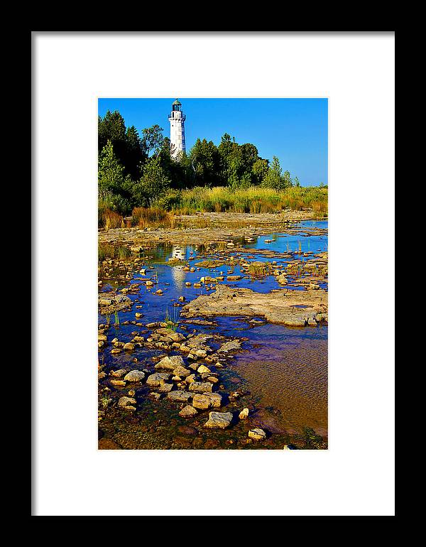 Cana Island Lighthouse Framed Print featuring the photograph The Cana Island Lighthouse In Baileys Harbor Reflective Waters. by Carol Toepke