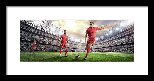 Soccer Uniform Framed Print featuring the photograph Soccer Player Kicking Ball In Stadium by Dmytro Aksonov