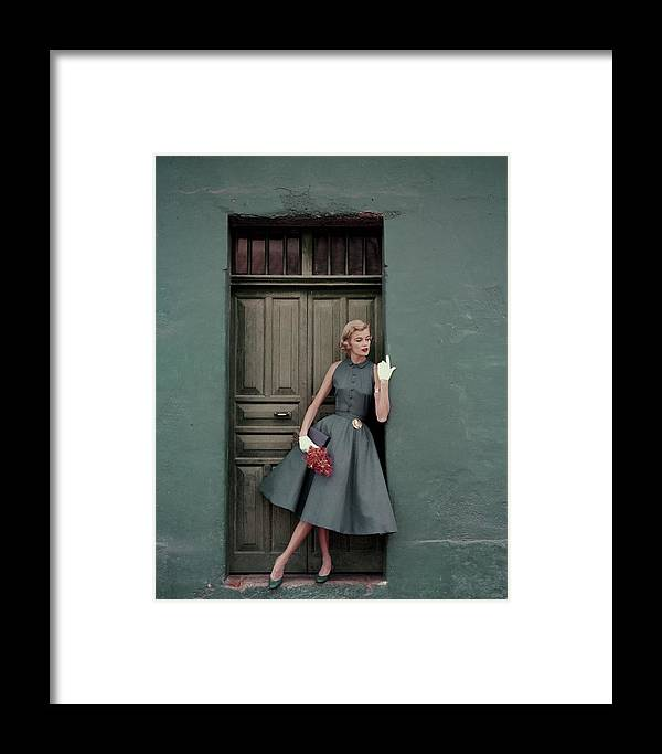 Fashion Framed Print featuring the photograph A 1950s Model Standing In A Doorway by Leombruno-Bodi