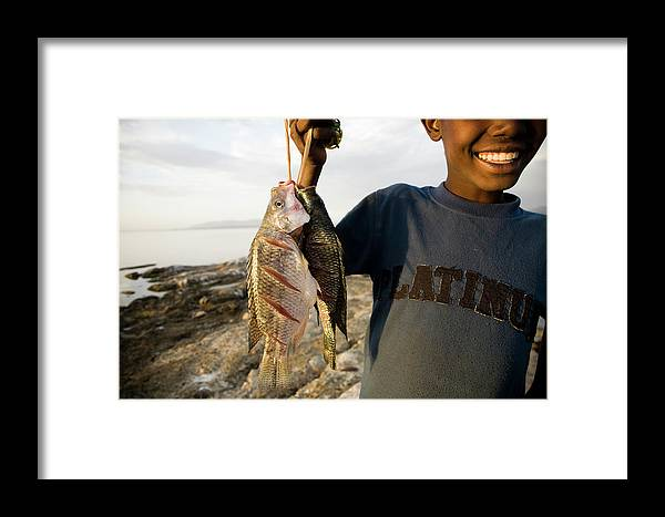 Africa Framed Print featuring the photograph A Boy Smiles While Holding A String by Michael Hanson