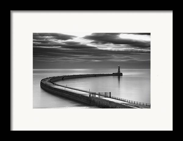 Lighthouse Framed Print featuring the photograph A Curving Pier With A Lighthouse At The by John Short