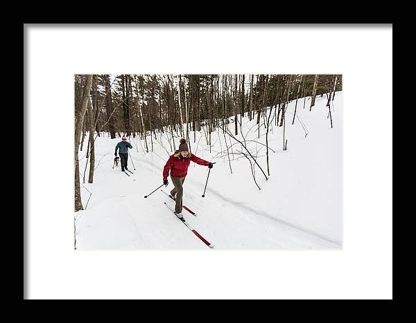 On The Move Framed Print featuring the photograph A Man And Woman Cross Country Skiing by Jerry Monkman