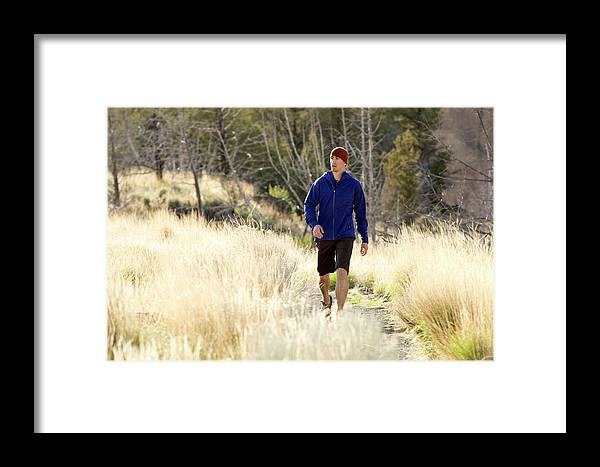 25-29 Years Framed Print featuring the photograph A Man In A Blue Jacket Walks by Jordan Siemens