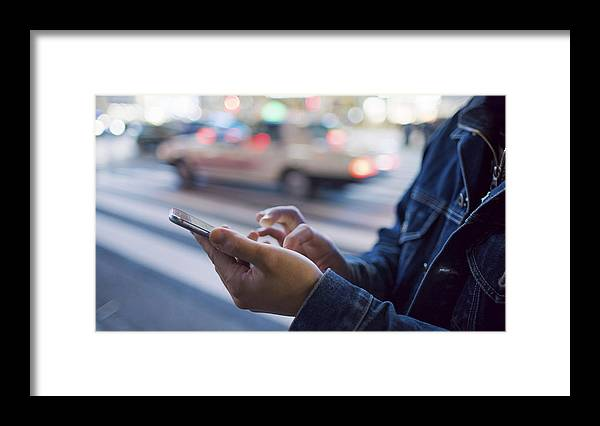 Young Men Framed Print featuring the photograph A man uses a mobile phone at Shibuya crossing by Bronek Kaminski