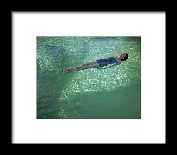 Exterior Framed Print featuring the photograph A Model Floating In A Swimming Pool by John Rawlings