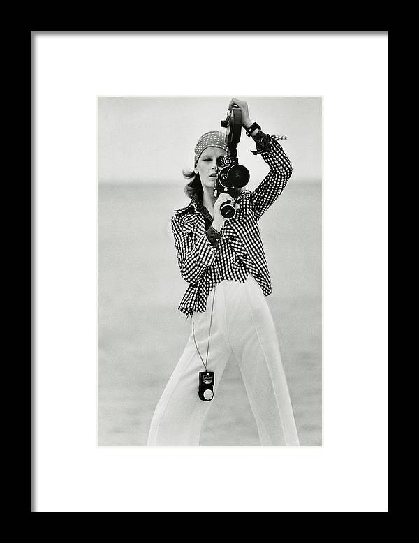 Fashion Framed Print featuring the photograph A Model Looking Through A Beaulieu Camera Wearing by Gianni Penati