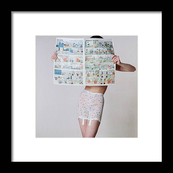 Fashion Framed Print featuring the photograph A Model Wearing A Girdle With A Comic by Louis Faurer