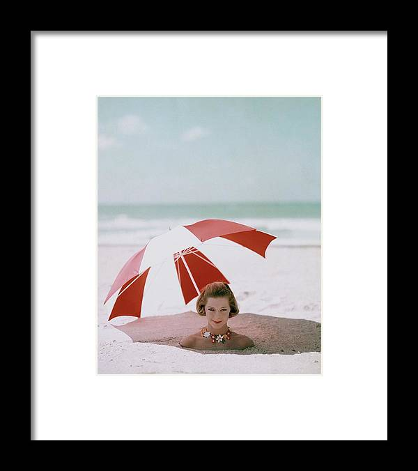 Beauty Framed Print featuring the photograph A Woman Buried In Sand At A Beach by Richard Rutledge