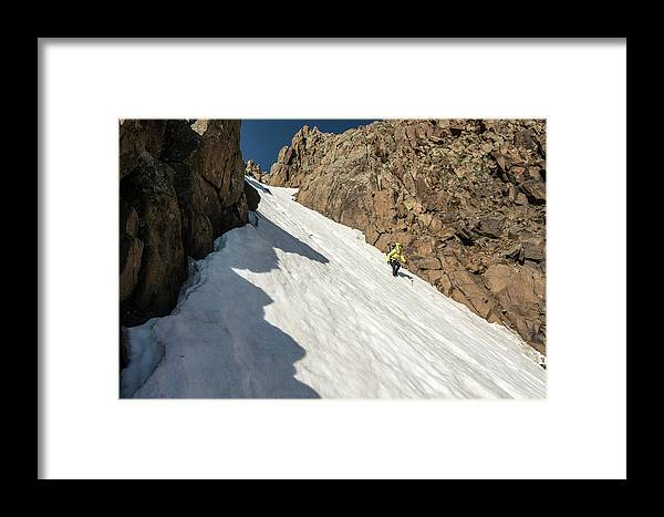 Low Angle View Framed Print featuring the photograph A Woman Descending A Snow Slope While by Kennan Harvey