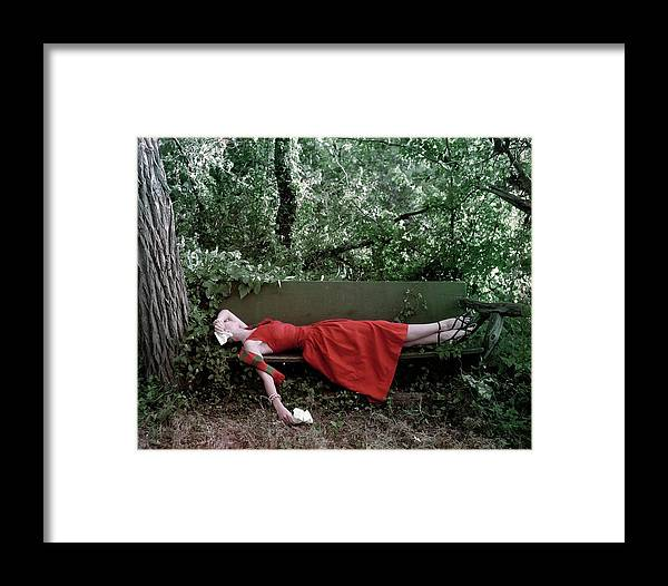 Accessories Framed Print featuring the photograph A Woman Lying On A Bench by John Rawlings