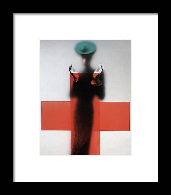 Fashion Framed Print featuring the photograph A Woman Standing Behind A Red Cross On Frosted by Erwin Blumenfeld