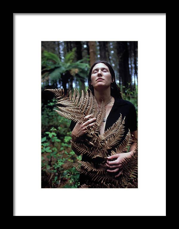 Calm Framed Print featuring the photograph A Young Woman Cradles A Fern Frond by Kyle George