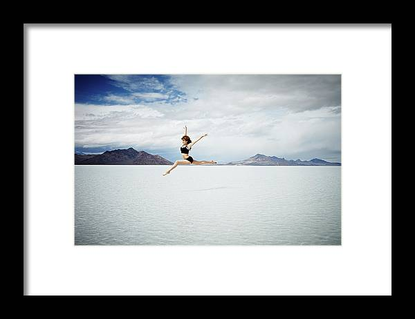 Ballet Dancer Framed Print featuring the photograph Ballerina Leaping In Mid-air Over Lake by Thomas Barwick
