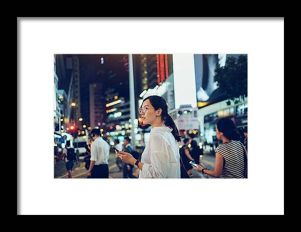 Financial Building Framed Print featuring the photograph Beautiful Asian woman using mobile phone while crossing road in busy downtown city street at night by D3sign