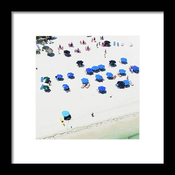 Water's Edge Framed Print featuring the photograph Blue Umbrellas On A Sunny Beach by Tommy Clarke