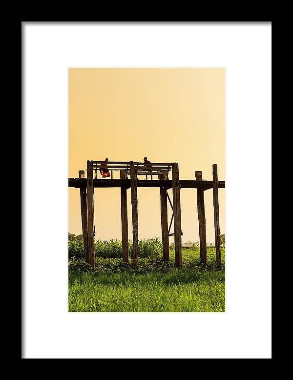 Grass Framed Print featuring the photograph Buddhist Monks Seated On U Bein Bridge by Merten Snijders
