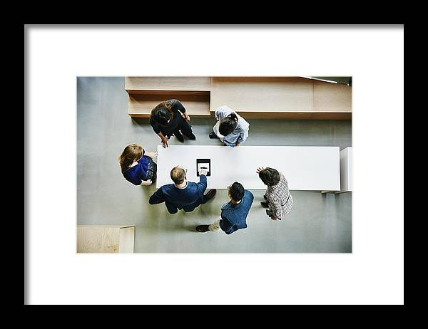Expertise Framed Print featuring the photograph Business colleagues discussing project in office by Thomas Barwick