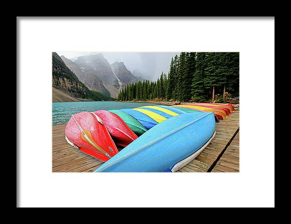 Scenics Framed Print featuring the photograph Canoes Line Dock At Moraine Lake, Banff by Wildroze
