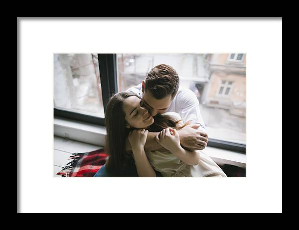 Young Men Framed Print featuring the photograph Caucasian couple hugging on bench near window by Kateryna Soroka