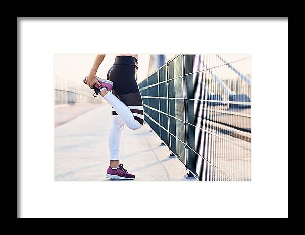Recreational Pursuit Framed Print featuring the photograph Close-up of woman stretching legs after running by Westend61