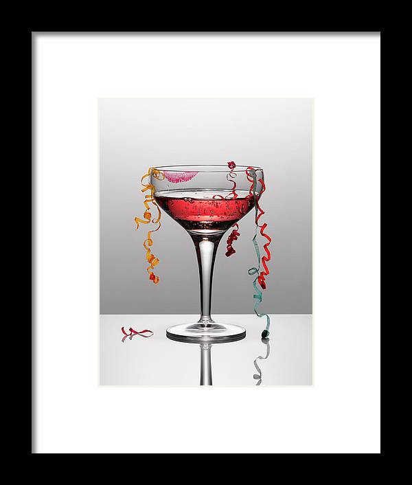 Streamer Framed Print featuring the photograph Confetti Hanging From Glass Of Pink by Andy Roberts