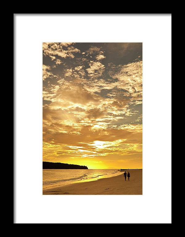 Scenics Framed Print featuring the photograph Couple Walking On Beach At Sunset by Richard I'anson