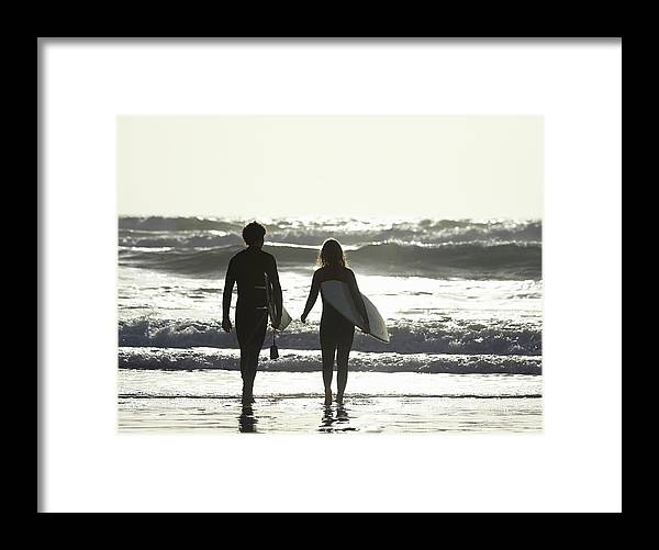Young Men Framed Print featuring the photograph Couple Walking Out To Sea With by Dougal Waters